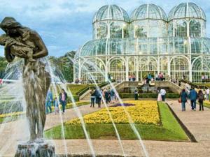 imagem do Jardim botânico de Curitiba com pessoas andando por ele