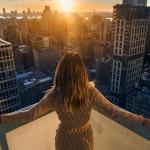 Mulher em arranha-céu vendo por do sol no horizonte