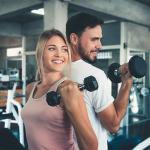 Homem de costas para mulher, ambos realizando exercícios