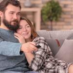 Casal no sofá assistindo séries
